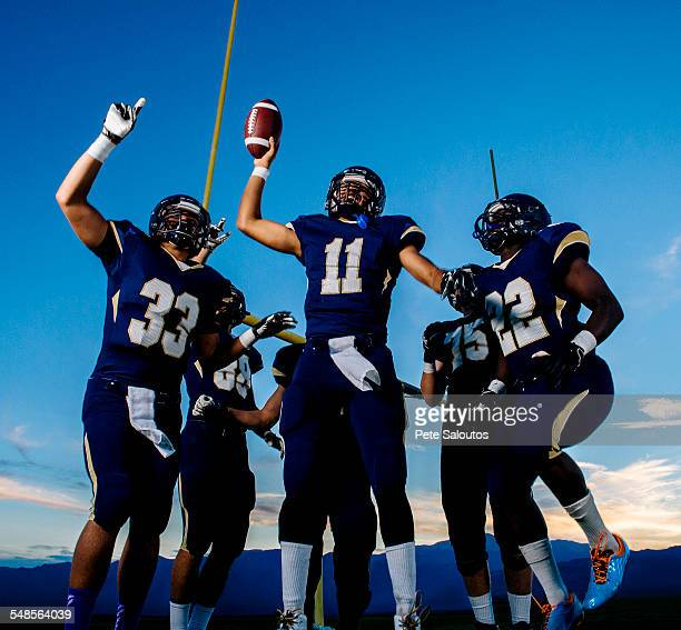 Teenage and young male american football team celebrating
