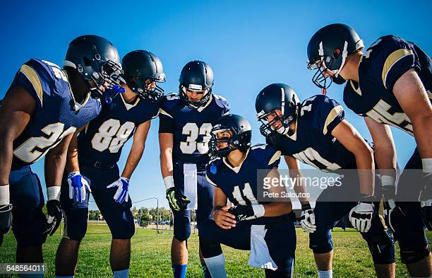 Teenage and young male American football team gathering and planning at practice