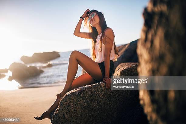 Jeune fille asiatique souriant sur les rochers au bord de la plage