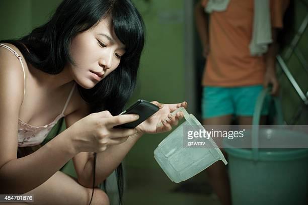 Junge asiatische Mädchen mit Handy während ihrer nationalen funktioniert.