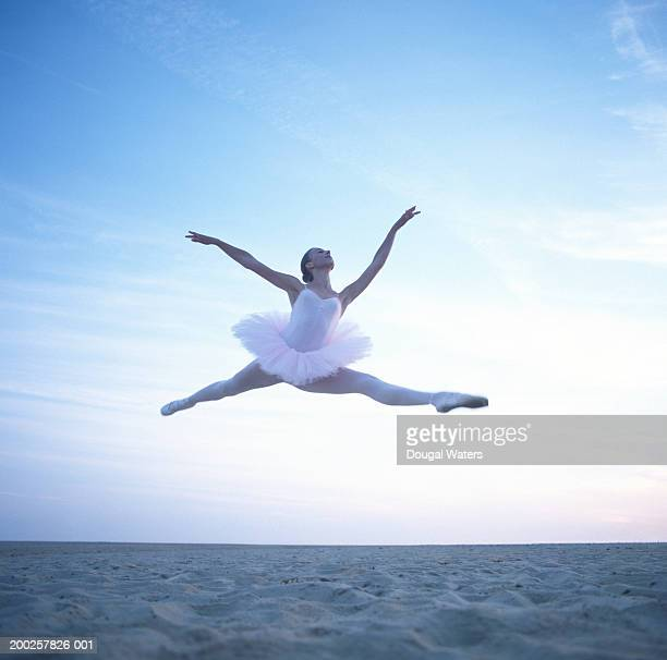 Teenage ballerina (16-18) performing leap on beach, low angle view