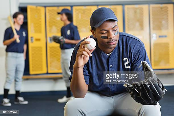 Teenage baseball pitcher in locker room after game