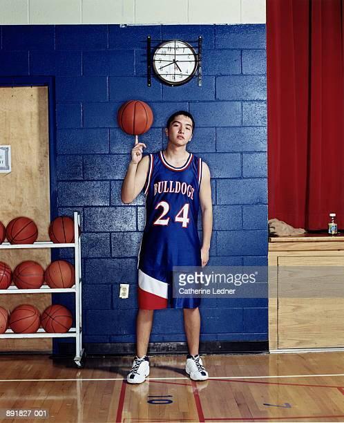 Teenage (16-18) basketball player balancing ball on finger
