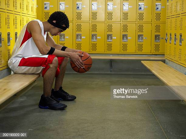 Teenage basketball player (14-16) sitting on bench in locker room