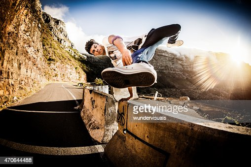 Teenage b-boy keeping fit practicing moves on a wall outdors