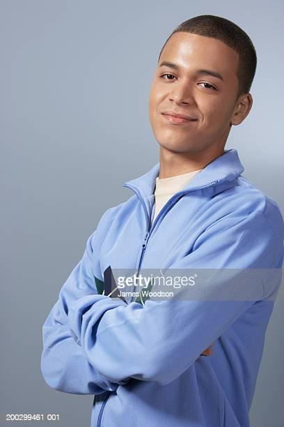 Teenage boy (16-18) against blue background, arms folded, portrait