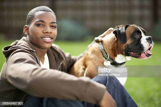 Teenage boy (14-16) and dog outdoors, boy smiling