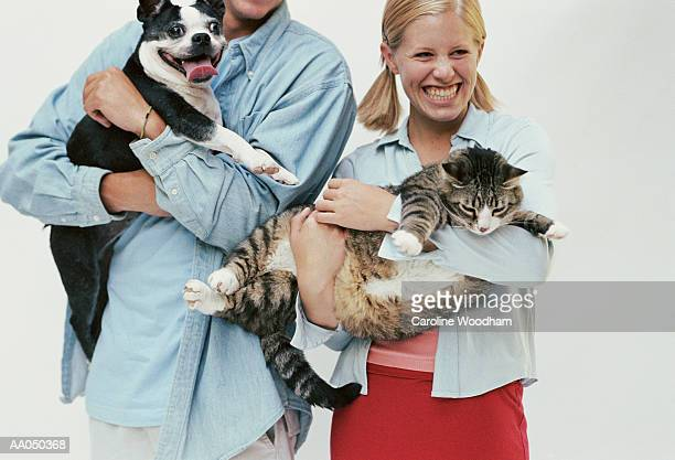 Teenage boy and girl (16-18) holding  cat and dog