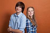 A teenage boy and girl, portrait, studio shot
