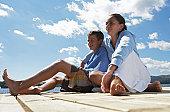 Teenage boy and girl (13-15) sitting on jetty