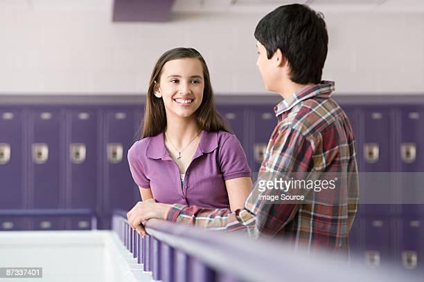 Teenage boy and girl talking in a corridor