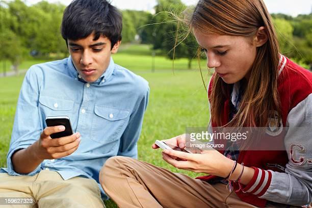 Teenage boy and girl using smartphones