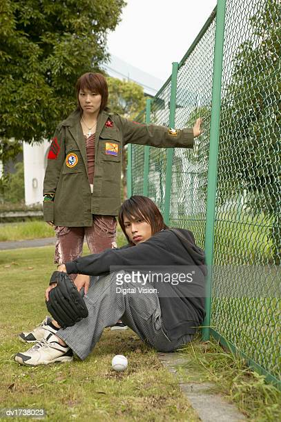 Teenage Boy and Girl With Attitude Sit and Stand by a Wire Fence, Boy Wearing a Baseball Glove