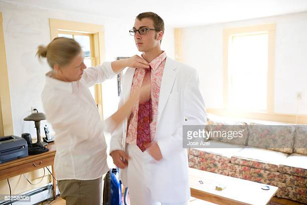 A teenage boy and his mother helping him get ready for prom night.