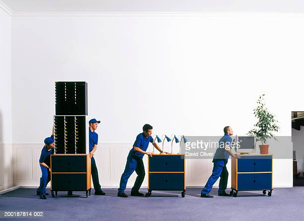 Teenage boy (14-16) and men in corridor, moving office furniture