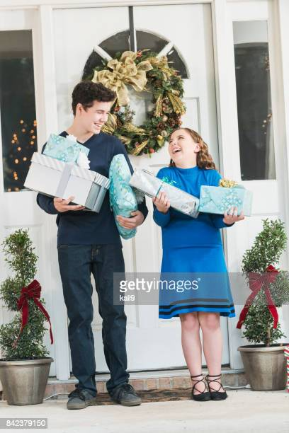 Teenage boy and sister carrying Christmas gifts