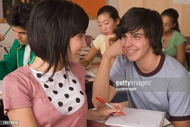 Teenage boy and teenage girl flirting in classroom