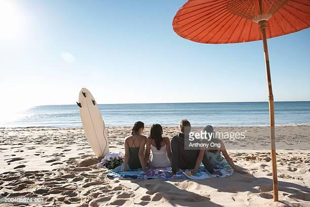 Teenage boy and three girls (15-18) by parasol on beach, rear view