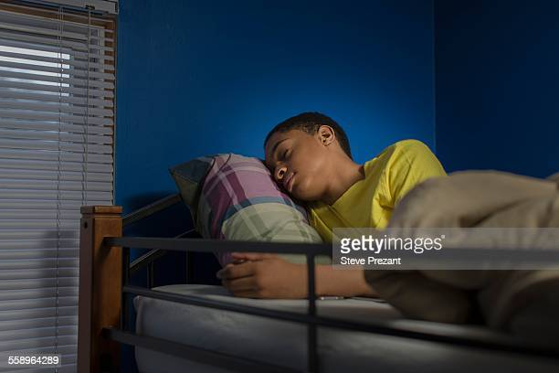 Teenage boy asleep in bunkbed