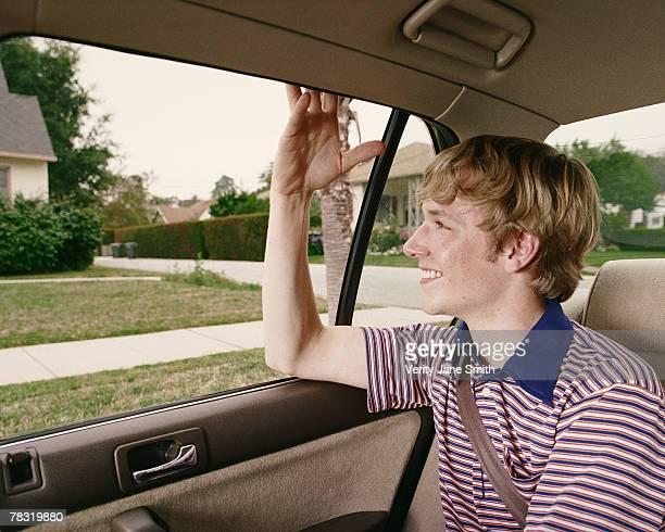 Teenage boy backseat of car