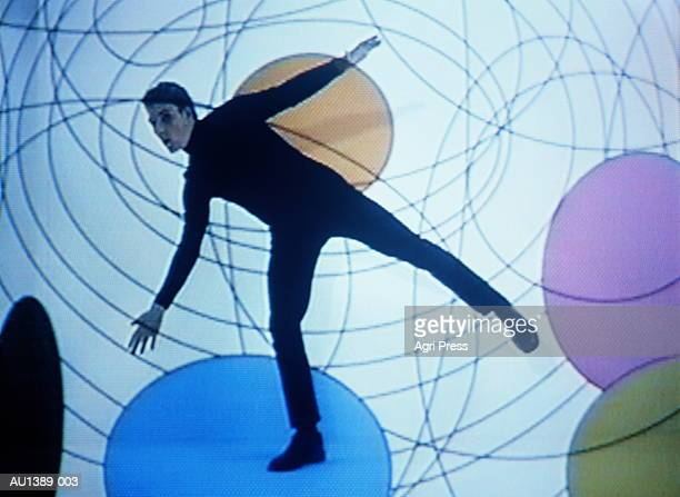 Teenage boy (17-19) balancing in design with circles (video still)