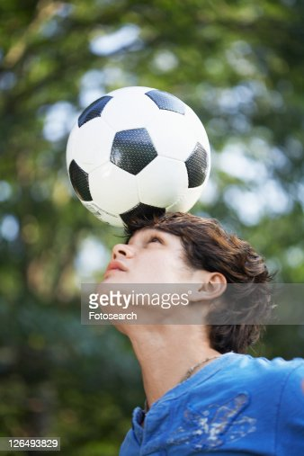 Teenage boy balancing soccer ball on forehead
