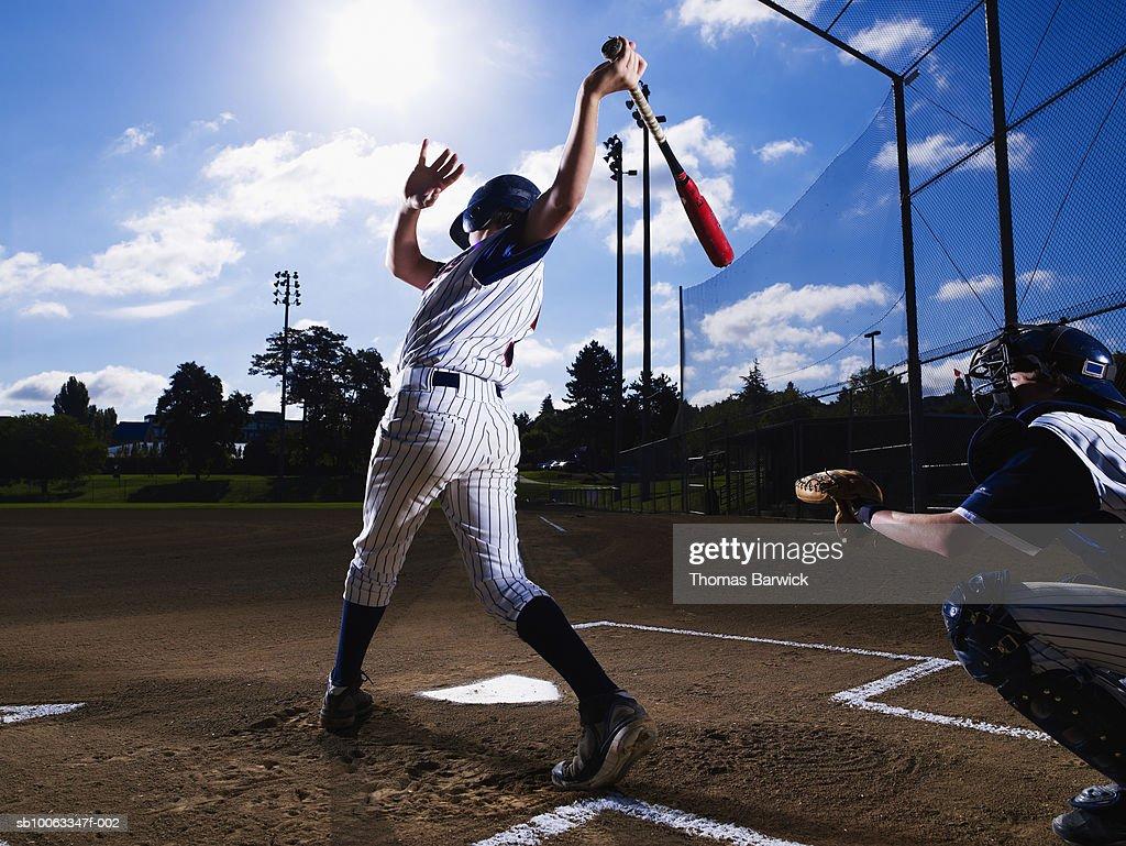 Teenage boy (13-14)  baseball player swinging bat, catcher behind him : Stock Photo