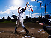 Teenage boy (13-14)  baseball player swinging bat, catcher behind him