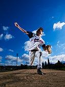 Teenage boy (13-14)  baseball player throwing pitch