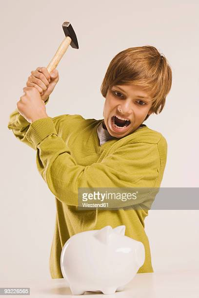 Teenage boy (14-15) about to smash piggy bank with hammer