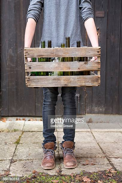 Teenage boy carrying empty bottles in wooden crate