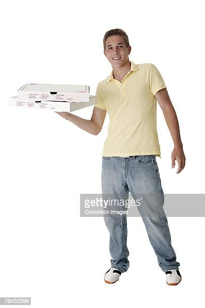 Teenage boy carrying pizza boxes