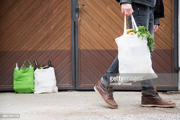 Teenage boy carrying reusable shopping bag full of fruit and veg, with bottles for recycling in yard