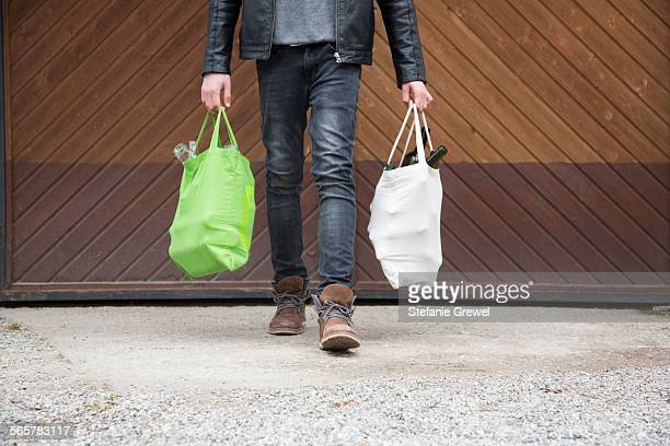 Teenage boy carrying reusable shopping bags full of empty bottles for recycling