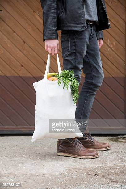 Teenage boy carrying reusable shopping bags full of fresh fruit and veg
