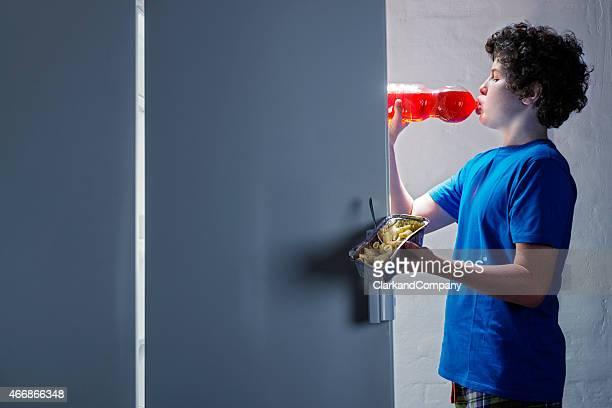 Ragazzo adolescente visto come uno spuntino a tarda notte dal frigorifero