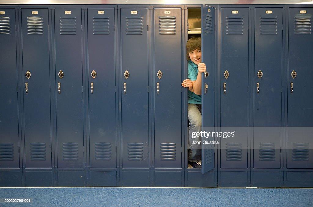 Teenage boy (13-15) coming out of locker