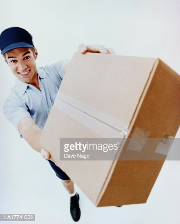 Teenage boy (17-19) delivering package, elevated view : Stock Photo