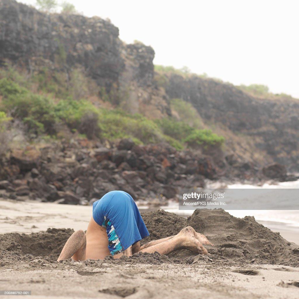 Teenage boy (12-14) digging hole on beach, sticking head in hole : Bildbanksbilder