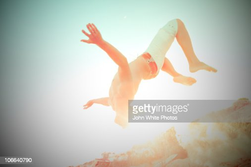 Teenage boy doing a back flip at beach : Stock Photo