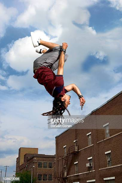 Teenage boy doing back flip in air
