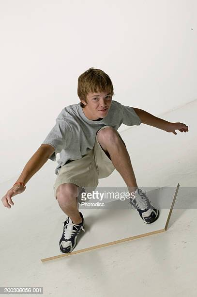 Teenage boy (16-17) doing surfing manoeuvre on plank of wood