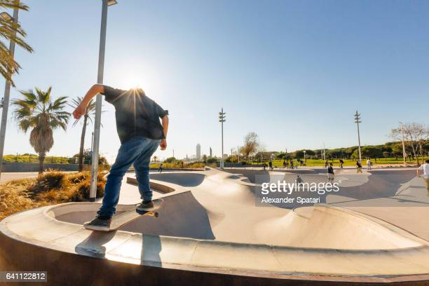 Teenage boy doing tricks with his skateboard in a skatepark on the beach