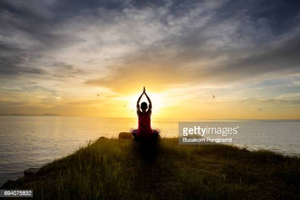 Teenage boy doing yoga at sunset