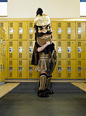 Teenage boy (15-17) dressed as mascot, in locker room, portrait