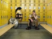 Teenage boy (15-17) dressed as mascot, seated in locker room, portrait