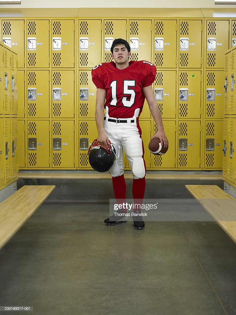 Teenage boy (16-18) dressed for football,  standing in locker room : Stock Photo