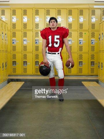 Teenage boy (16-18) dressed for football,  standing in locker room : Photo