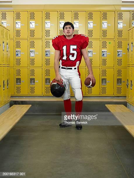 Teenage boy (16-18) dressed for football,  standing in locker room