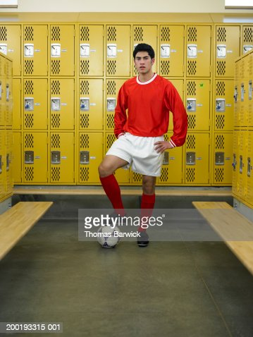 Teenage boy (16-18) dressed for soccer, standing in locker room : Stock Photo